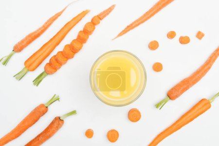 Photo for Top view of carrot slices, whole and cut carrots and bowl of fresh carrot juice in center isolated on white - Royalty Free Image