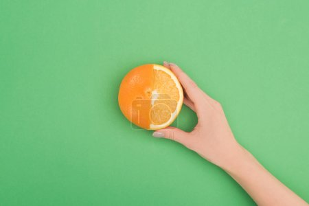 Photo for Cropped view of female hand with fresh partially cut orange on green background - Royalty Free Image