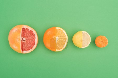 top view of fresh partially cut grapefruit, orange, lemon and tangerine on green background