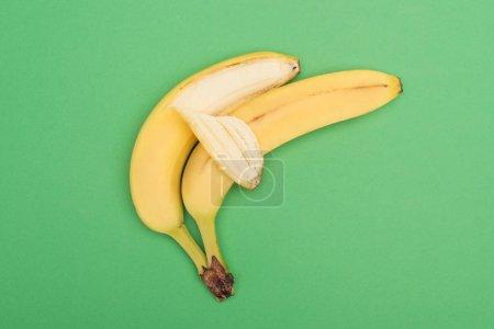 Foto de Vista superior de plátanos jugosos maduros frescos sobre fondo verde - Imagen libre de derechos