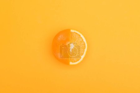 Photo for Top view of fresh ripe partially cut orange on orange background - Royalty Free Image