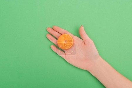 Photo pour Vue partielle de la main féminine avec partiellement coupé mandarine sur fond vert - image libre de droit