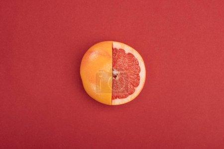 Foto de Vista superior del fresco maduro cortado parcialmente pomelo sobre fondo rojo - Imagen libre de derechos