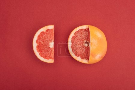 Photo for Top view of grapefruit slice and partially cut grapefruit on red background - Royalty Free Image