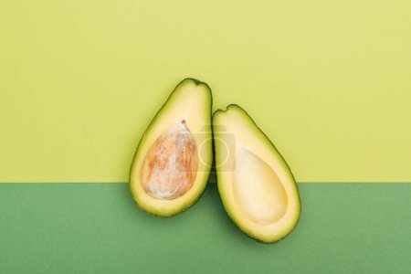 Photo for Top view of fresh ripe avocado halves on bicolor background - Royalty Free Image