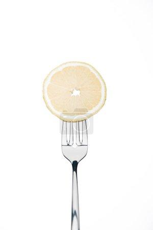 Photo for Sircle slice of fresh ripe juicy lemon on fork isolated on white - Royalty Free Image