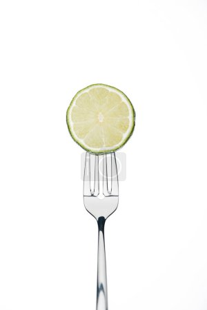 Photo for Circle slice of fresh ripe juicy lime on fork isolated on white - Royalty Free Image