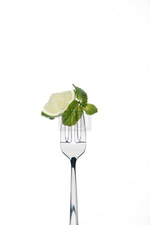 Photo pour Tranche de citron vert et menthe laisse sur fourche isolé sur blanc - image libre de droit