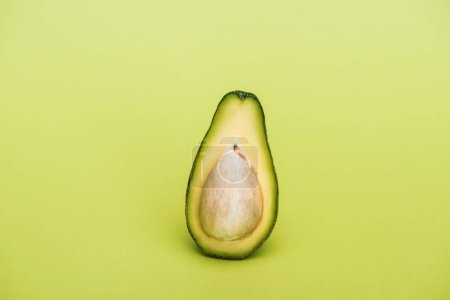 Photo for Half of ripe fresh tasty avocado on green background - Royalty Free Image