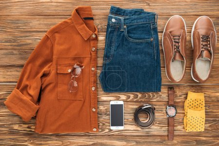 Photo for Flat lay with smartphone and male clothes on wooden background - Royalty Free Image
