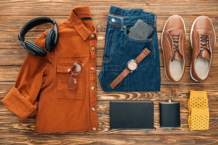 Photo for Flat lay with headphones, hip flask and male clothes on wooden background - Royalty Free Image
