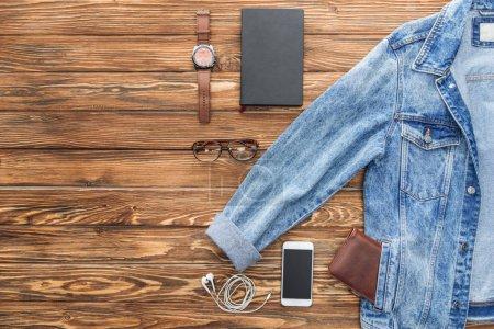 Photo pour Plat poser avec la veste en Jean, smartphone et accessoires sur fond en bois - image libre de droit