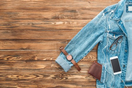 Photo for Top view of denim jacket, wristwatch and smartphone on wooden background - Royalty Free Image