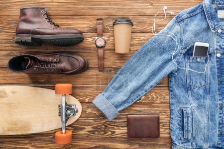 Photo for Flat lay with denim jacket, boots and longboard on wooden background - Royalty Free Image