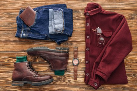 Photo for Flat lay with shirt, jeans and leather accessories on wooden background - Royalty Free Image