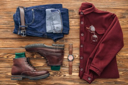 Photo for Flat lay with leather boots, jeans and shirt on wooden background - Royalty Free Image