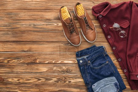 Photo for Flat lay with boots, shirt and jeans on wooden background - Royalty Free Image