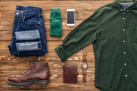 Photo for Flat lay with jeans, green shirt and smartphone on wooden background - Royalty Free Image
