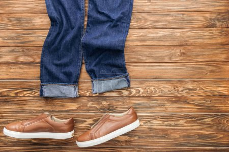 Photo for Top view of jeans and brown shoes on wooden background - Royalty Free Image