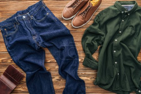 Photo for Top view of jeans, brown shoes and green shirt on wooden background - Royalty Free Image