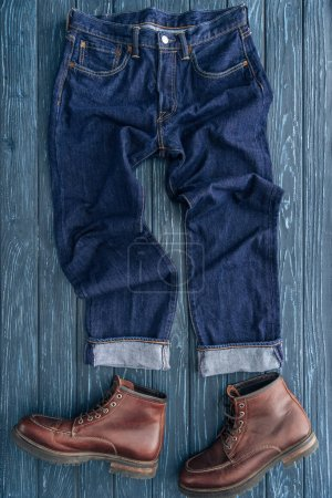 Photo for Top view of jeans and brown leather boots on wooden background - Royalty Free Image
