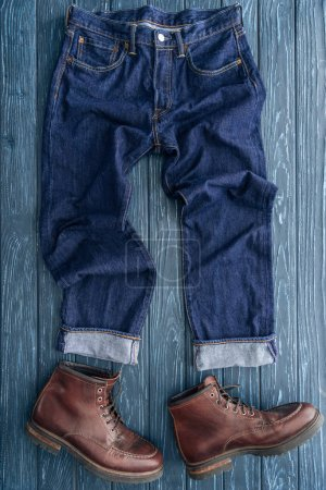 Photo for Top view of jeans and leather boots on wooden background - Royalty Free Image