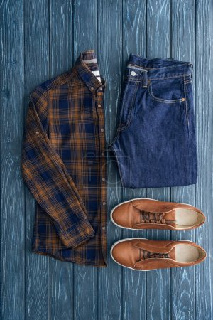 Photo for Top view of checkered shirt, jeans and brown shoes on wooden background - Royalty Free Image