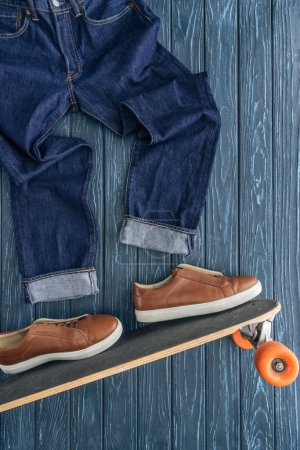 Photo for Top view of jeans, brown shoes and longboard on wooden background - Royalty Free Image