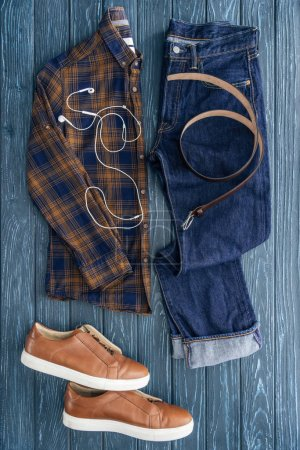 Photo for Top view of jeans, checkered shirt and earphones on wooden background - Royalty Free Image
