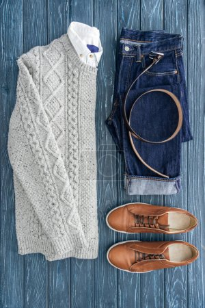 Photo for Flat lay with knitted sweater, jeans and brown shoes on wooden background - Royalty Free Image