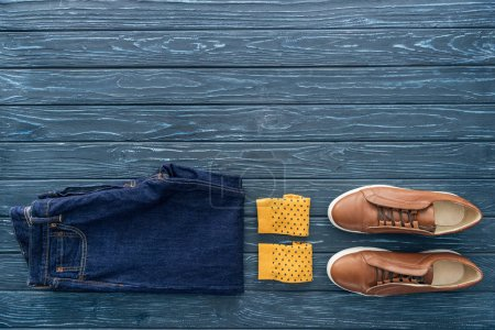 Photo for Top view of jeans, yellow socks and boots on wooden background - Royalty Free Image