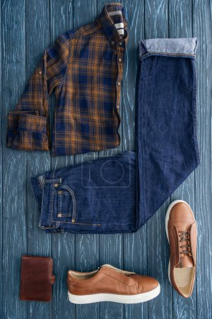 Photo for Flat lay with checkered shirt, jeans and boots on wooden background - Royalty Free Image