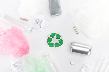 Top view of cans, plastic bags, paper, recycling sign, plastic and glass bottles