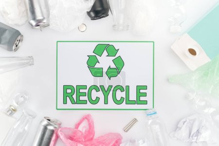 Cans, plastic and glass bottles, batteries, paper, bulb, carton bottle and plastic bags with recycling sign
