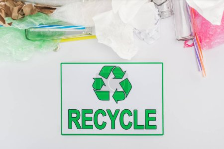 Glass bottles, plastic bags, paper and plastic tubes with recycling sign on grey background