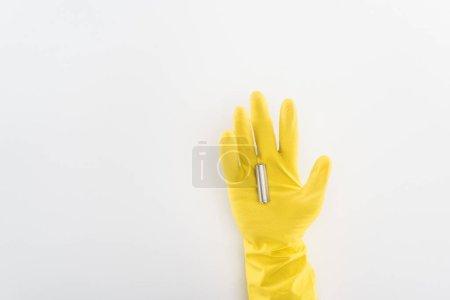 Photo pour Vue recadrée de l'homme en gants de caoutchouc jaune tenant la batterie sur fond gris - image libre de droit