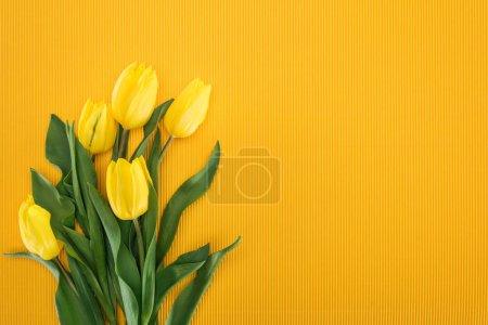Photo pour Vue du haut du bouquet avec des tulipes jaunes sur fond orange - image libre de droit