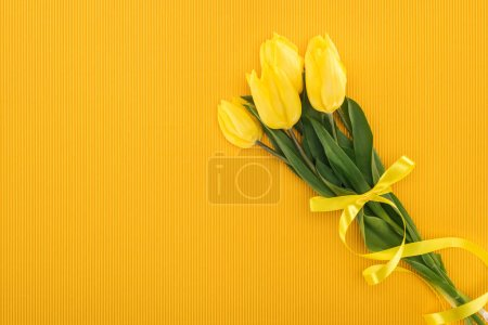 top view of yellow tulip bouquet with ribbon on orange background for international womens day