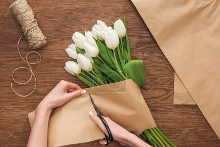 Photo for Partial view of on florist cutting craft paper while making spring bouquet on wooden background - Royalty Free Image