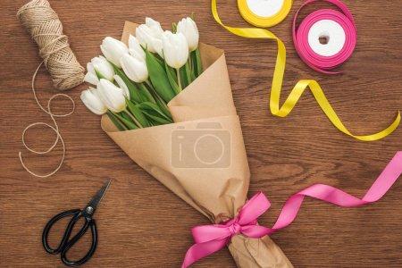 Photo pour Vue de dessus du bouquet de tulipes de printemps avec du papier de rubans et de l'artisanat sur fond en bois - image libre de droit