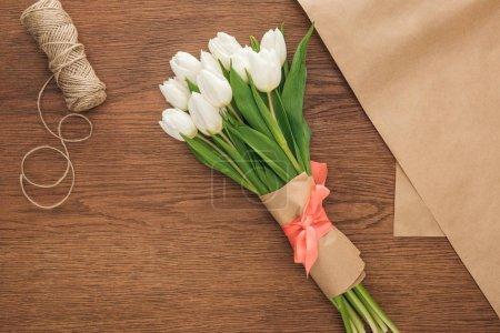 Photo pour Vue de dessus de printemps tulipes bouquet et l'artisanat papier sur fond en bois - image libre de droit