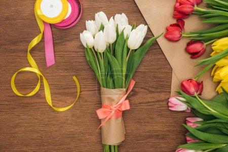 Photo pour Vue de dessus du papier bouquet, de tulipes, de rubans et d'artisanat de printemps sur fond en bois - image libre de droit