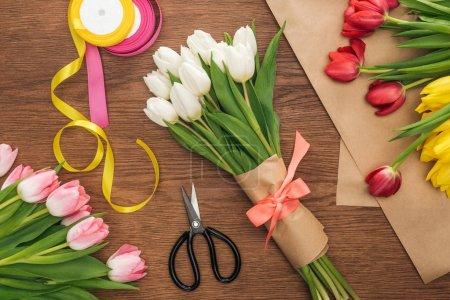 Photo pour Vue de dessus du papier bouquet, de tulipes, de rubans et d'artisanat d'art floral sur fond en bois - image libre de droit