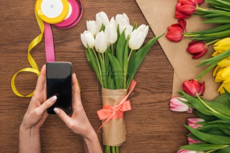 Photo for Cropped view of on florist using smartphone near spring bouquet with tulips on wooden background - Royalty Free Image