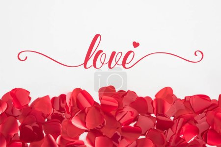 "Photo for Close-up view of beautiful red heart shaped petals on grey background with ""love"" lettering, valentines day concept - Royalty Free Image"