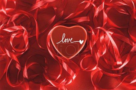 """vue rapprochée de beau coeur rouge avec lettrage """"amour"""" et rubans décoratifs, fond de Saint-Valentin"""
