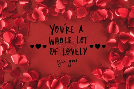 "top view of decorative heart shaped petals on red background with ""you are a whole lot of lovely, yes you"" lettering, valentines day concept"