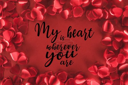 "Photo for Top view of decorative heart shaped petals on red background with ""my heart is wherever you are"" lettering, valentines day concept - Royalty Free Image"