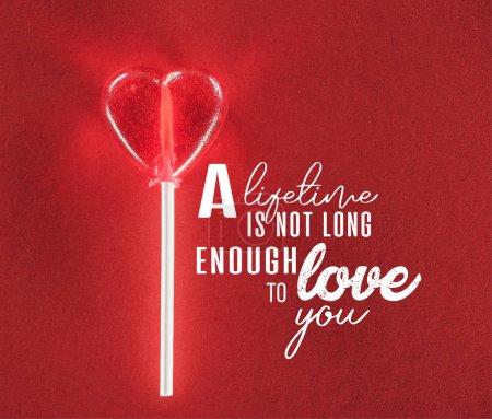 Photo pour Vue rapprochée du coeur en forme de bonbons sur fond rouge avec lettrage «sa vie n'est pas assez long à t'aimer», notion de Valentin - image libre de droit