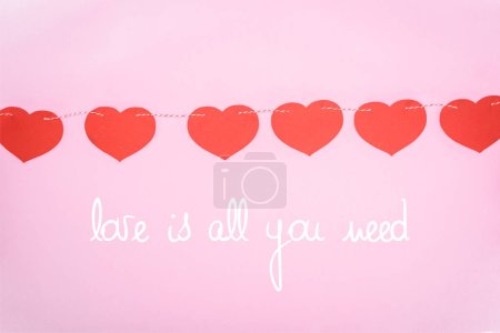"""Photo for Beautiful decorative red hearts hanging on rope on pink background with """"Love is all you need"""" lettering, valentines day concept - Royalty Free Image"""